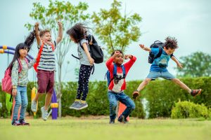 Kids Jumping Outside With Backpacks