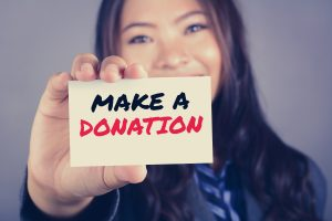 Lady Holding a Make A Donation Sign